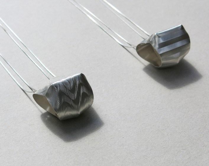 zwei kleinere Ketten (Anhänger ca. 7cm hoch) aus Silber, guillochiert